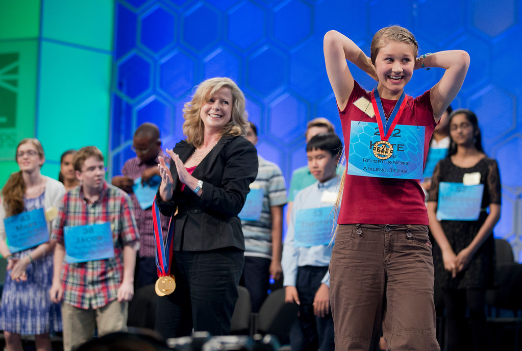. Eighth grade home-schooled student Kate Miller, 14, of Abilene, Texas, right, celebrates after making it to the finals of the Scripps National Spelling Bee, Thursday, May 29, 2014, at National Harbor in Oxon Hill, Md. Applauding in the center is Paige Kimble, executive director of the Scripps National Spelling Bee.   (AP Photo/Manuel Balce Ceneta)