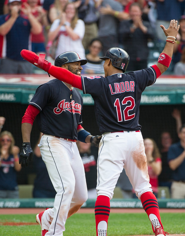 . Cleveland Indians\' Francisco Lindor greets Austin Jackson after Jackson scored on a throwing error by Kansas City Royals\' Drew Butera during the sixth inning of a baseball game in Cleveland, Saturday, Sept. 16, 2017. (AP Photo/Phil Long)