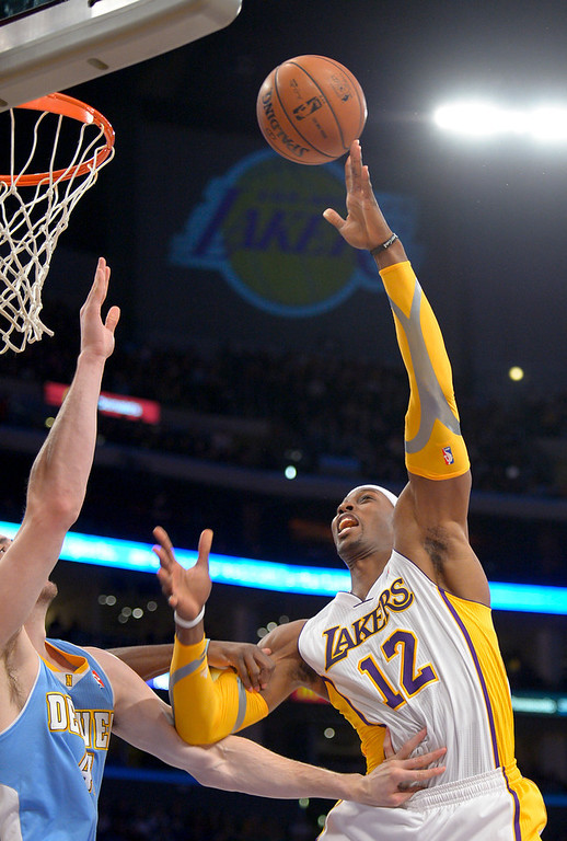 . Los Angeles Lakers center Dwight Howard, right, shoots over Denver Nuggets\' Kosta Koufos during the first half of their NBA basketball game, Sunday, Jan. 6, 2013, in Los Angeles. (AP Photo/Mark J. Terrill)