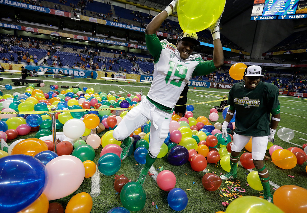 . Oregon\'s Tyrell Robinson (19) plays in balloons as he celebrates the team\'s win over Texas in the Valero Alamo Bowl NCAA college football game, Monday,  Dec. 30, 2013, in San Antonio. Oregon won 30-7. (AP Photo/Eric Gay)