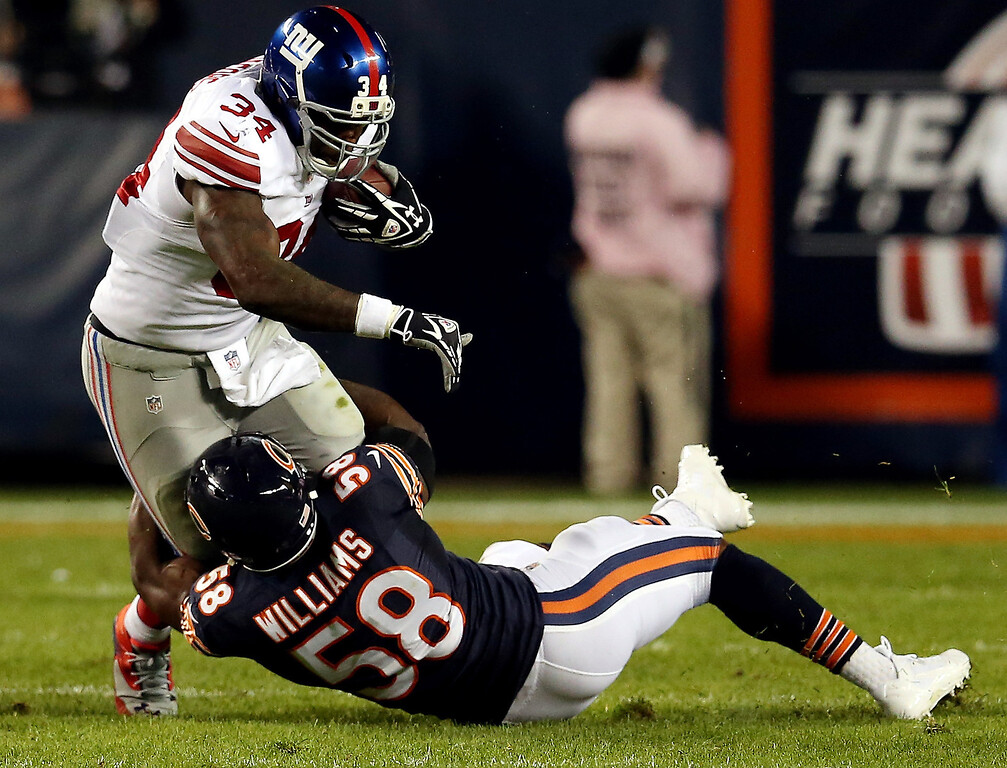. Running back Brandon Jacobs #34 of the New York Giants is tackled by middle linebacker D.J. Williams #58 of the Chicago Bears during a game at Soldier Field on October 10, 2013 in Chicago, Illinois.  (Photo by Jonathan Daniel/Getty Images)