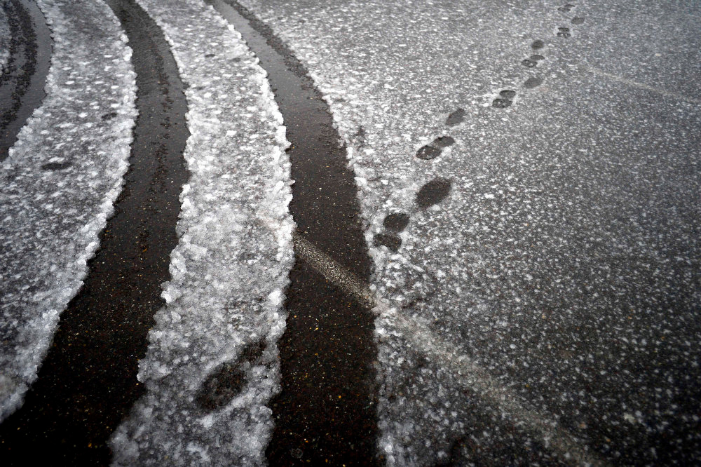 . Tire tracks and footprints are left in the parking lot of Yowell Meadow park in Culpeper, Va. An overnight storm brought rain, snow and ice to the Culpeper area on Wednesday, Dec. 26 2012. (AP Photo/The Free Lance-Star, Reza A. Marvashti)