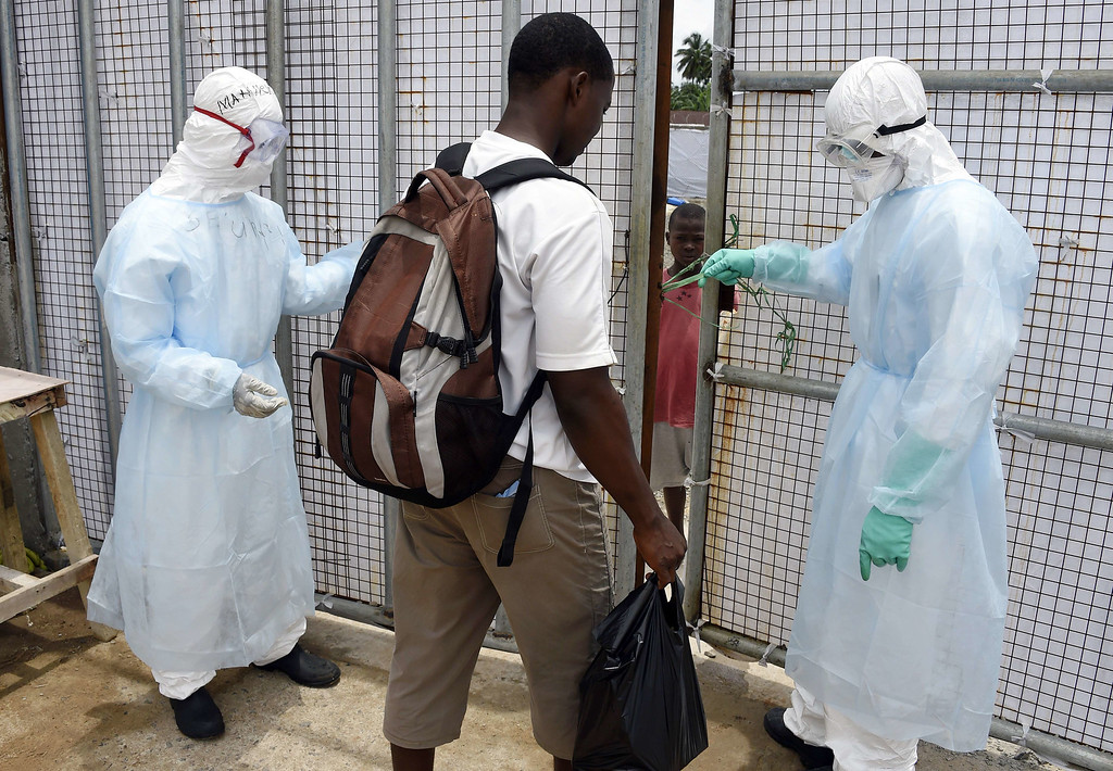 . Health workers slightly open the gate of Island Hospital in order to allow a man to deliver food to his son suffering from the Ebola virus in Monrovia on September 26, 2014. PASCAL GUYOT/AFP/Getty Images