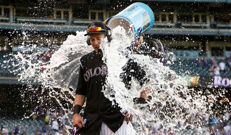 . Colorado Rockies\' Drew Stubbs, front, is doused with a water bucket by teammate Brandon Barnes as Stubbs is interviewed after hitting a three-run, wlakoff home run against the Cincinnati Reds in the ninth inning of the Rockies\' 10-9 victory in a baseball game in Denver on Sunday, Aug. 17, 2014. (AP Photo/David Zalubowski)