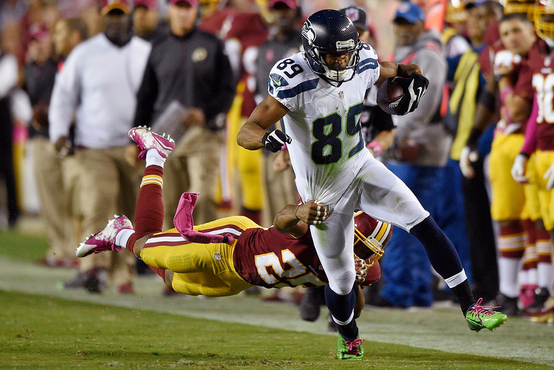 . Washington Redskins strong safety Bashaud Breeland (26) hangs on to Seattle Seahawks wide receiver Doug Baldwin (89) during the first half of an NFL football game in Landover, Md., Monday, Oct. 6, 2014. (AP Photo/Nick Wass)
