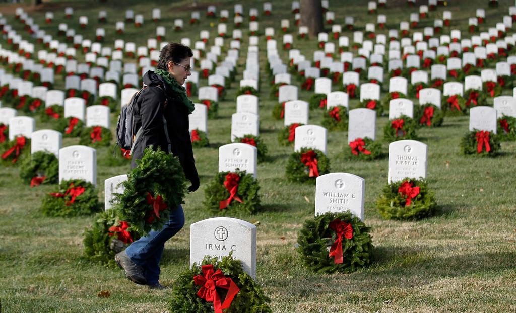 . A unidentified woman walks with a holiday wreaths during Wreaths Across America\'s 150th anniversary, Saturday, Dec. 13, 2014, at Arlington National Ceretery in Arlington, Va. (AP Photo/Luis M. Alvarez)
