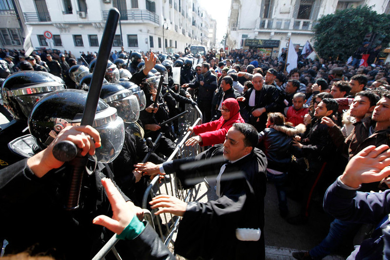 . Tunisian protesters clash with riot police slogans during a demonstration after the death of Tunisian opposition leader Chokri Belaid, outside the Interior ministry in Tunis February 6, 2013. Tunisia\'s secular opposition Popular Front said it was pulling out of the constituent assembly charged with writing a constitution after an opposition politician was killed on Wednesday. REUTERS/Anis Mili