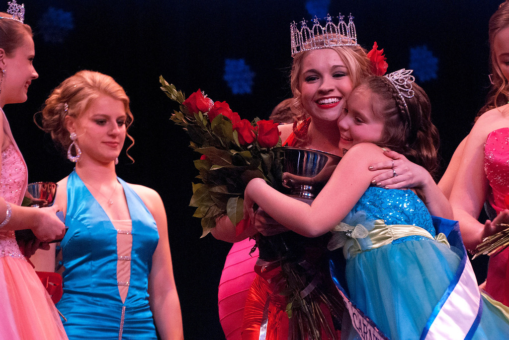 . Kayla Rice/Reformer Kara Walsh gets a hug from 2013 Winter Carnival Princess Kyla Brown after being announced as the 2014 Winter Carnival Queen during the Queen\'s pageant on Friday evening.