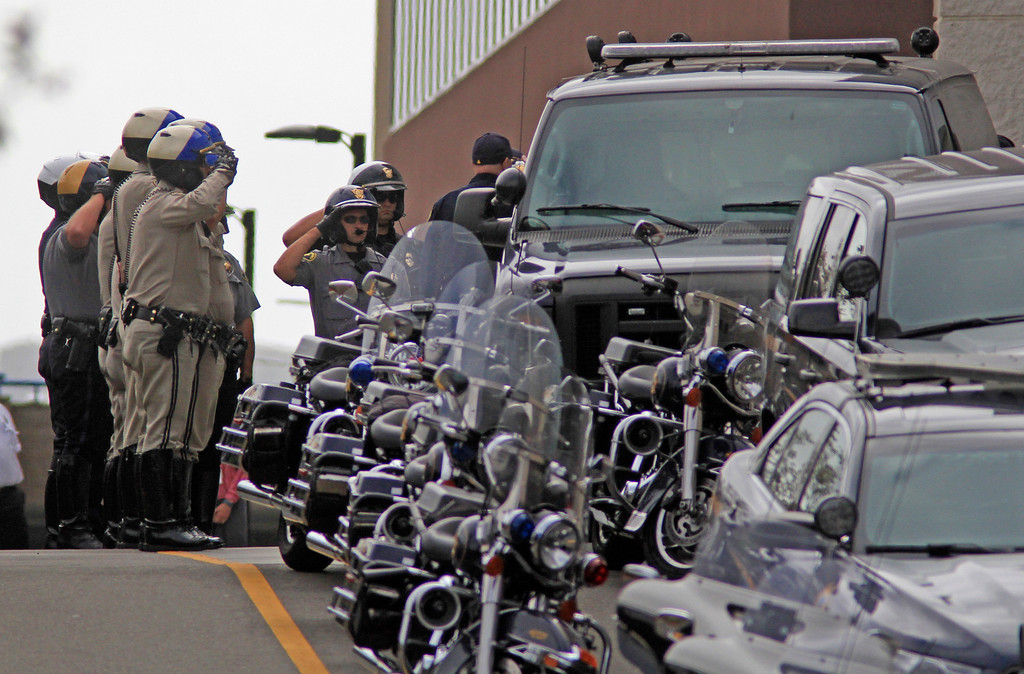 . Local law enforcement salute as the Alameda County Coroner prepares to leave Eden Medical Center with the body of Hayward police Sgt. Scott Lunger escorted  by Hayward Police and California Highway Patrol in Castro Valley, Calif., on Wednesday, July 22, 2015.  (Laura A. Oda/Bay Area News Group)