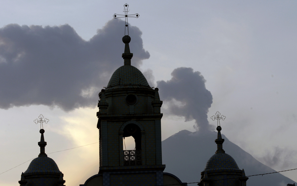 Description of . Church steeples are silhouetted against the active Tungurahua volcano, seen from Huambalo, Ecuador, Monday, Dec. 17, 2012.  The country's National Geophysics Institute says that a constant plume of gas and ash is rising about half a mile (1 kilometer) above the crater, with ash falling on nearby communities.  (AP Photo/Dolores Ochoa)