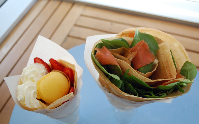 a photo of two wrapped crepes, one with whipped cream and the other with salmon and spinach
