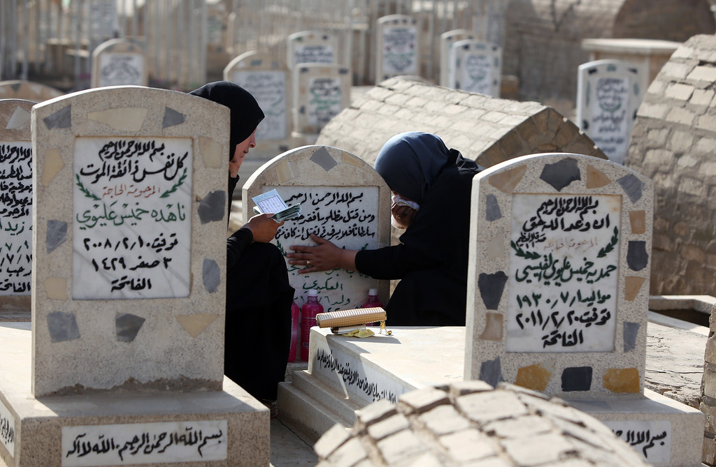 """. Iraqi women visit the grave of a loved one at a cemetery in the capital Baghdad during the first day of the Muslim Eid al-Adha holiday or \""""The Feast of Sacrifice\"""" on October 15, 2013.   AFP PHOTO/AHMAD AL-RUBAYE/AFP/Getty Images"""