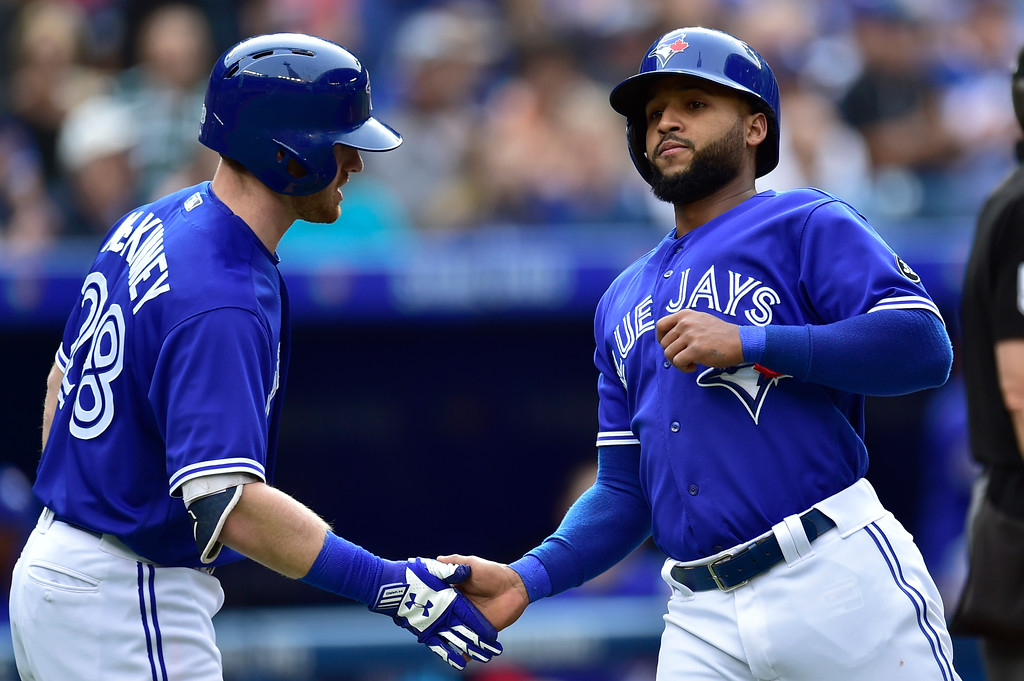 . Toronto Blue Jays\' Richard Urena, right, is congratulated by Billy McKinney  after scoring a run against the Cleveland Indians during the second inning of a baseball game in Toronto, Saturday, Sept .8, 2018. (Frank Gunn/The Canadian Press via AP)