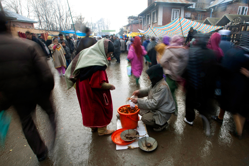 . A Kashmiri woman buys pickles from a roadside vendor after offering prayers at the Hazratbal shrine on Eid-e-Milad, or birth anniversary of Prophet Muhammad, in Srinagar, India, Tuesday, Jan. 14, 2014. Thousands of Kashmiri Muslims gathered at the Hazratbal shrine, which houses a relic believed to be a hair from the beard of the prophet. (AP Photo/Dar Yasin)