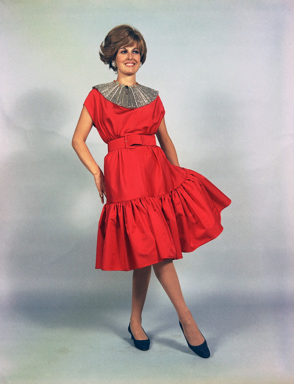 . A cocktail dress of red faille, trimmed around the neckline with golden jewelry, and with a very full swinging low-placed double gown. The dress, named �Tommaso�, is a creation by the Eleanora Garnett fashion house of Rome, July 13, 1968, to be presented at its show of fall and winter fashions on July 14. (AP Photo/Mario Torvist)