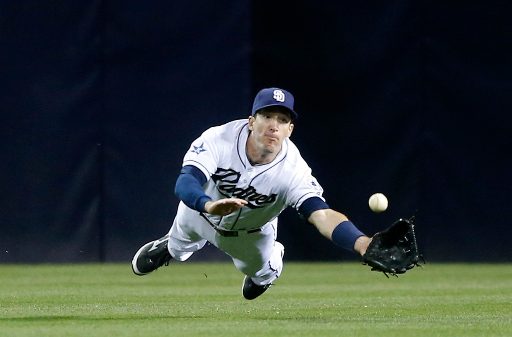 . San Diego Padres center fielder Chris Denorfia makes the diving attempt to catch a bloop double hit by Colorado Rockies\' Justin Morneau in the fourth inning of a baseball game Wednesday, April 16, 2014, in San Diego.  The ball came loose when Denorfia hit the ground.  (AP Photo/Lenny Ignelzi)