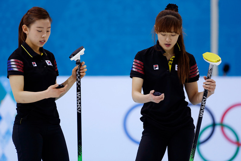 . South Korea\'s Um Min-ji and Gim Un-Chi start their stopwatches as they time a Switzerland throw during women\'s curling competition at the 2014 Winter Olympics, Tuesday, Feb. 11, 2014, in Sochi, Russia. (AP Photo/Robert F. Bukaty)