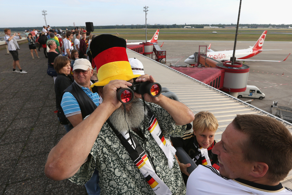 . A German fan uses binoculars as he stands on the visitors terrace at Berlin airport Tegel on July 15, 2014, where the plane of German national football team is expected on their way back from Brazil after they won the FIFA World Cup 2014. The team comes to Berlin for a victory parade at landmark Brandenburg Gate to celebrate their fourth World Cup title, after their 1-0 win over Argentina on July 13, 2014 in Rio de Janeiro in the FIFA World Cup Brazil final game. (ADAM BERRY/AFP/Getty Images)