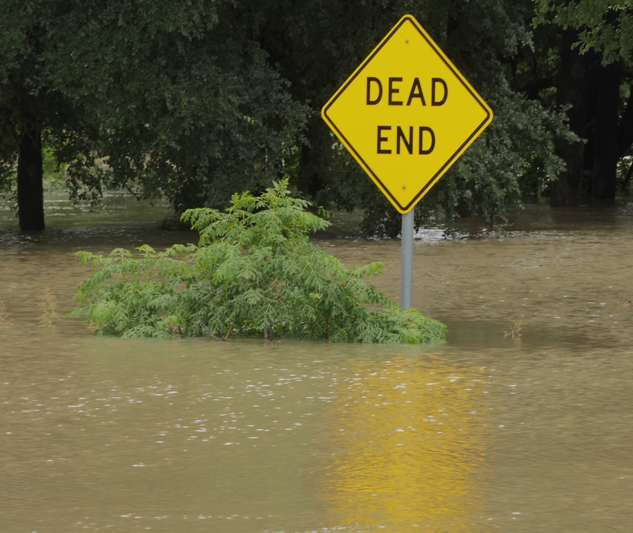 . A street sign covered by flood waters informs where a service roads ends near Sunset Golf Course along east Main Street in Grand Prairie, Texas, Friday, May 29, 2015. Floodwaters submerged highways and threatened homes Friday in Texas as another round of heavy rain added to the damage inflicted by recent storms. (Ron Baselice/The Dallas Morning News)