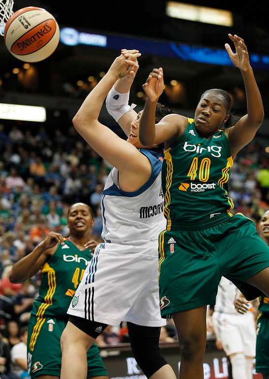 . Minnesota Lynx forward Janel McCarville (4) and Seattle Storm guard Shekinna Stricklen (40) fight for a rebound in the first half of a WNBA basketball game, Sunday, Aug. 4, 2013, in Minneapolis. (AP Photo/Stacy Bengs)