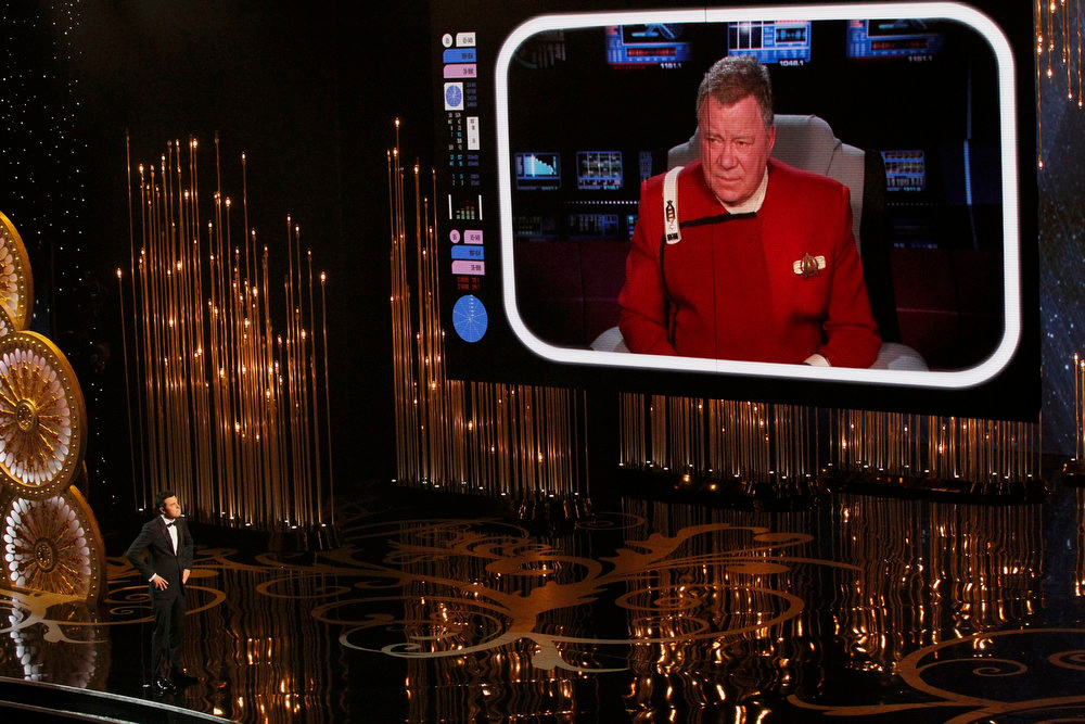 Description of . Oscar host Seth MacFarlane watches William Shatner on a screen during the opening segment of the 85th Academy Awards in Hollywood, California February 24, 2013.   REUTERS/Mario Anzuoni