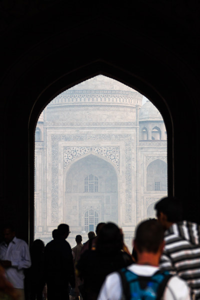 The gate of the Taj Mahal as seen from the main entrance to the grounds with many tourists entering.