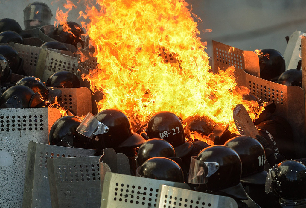 . Riot policemen in flames clash with protesters during the continuing protest in downtown Kiev, Ukraine, 18 February 2014. A least three protesters were killed in clashes with police on 18 February, Ukrainian opposition activists say.  EPA/ANDREW KRAVCHENKO