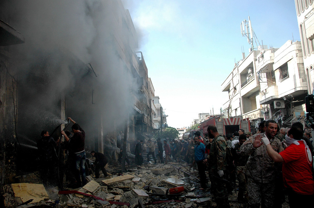 . People and rescuers gather at the scene of a car bomb along al-Khudary Street in the Karm al-Loz neighborhood in the Syrian city of Homs on April 9, 2014. More than 150,000 people have been killed in Syria since the conflict began in March 2011, a monitoring group said in a new toll released. (AFP/Getty Images)