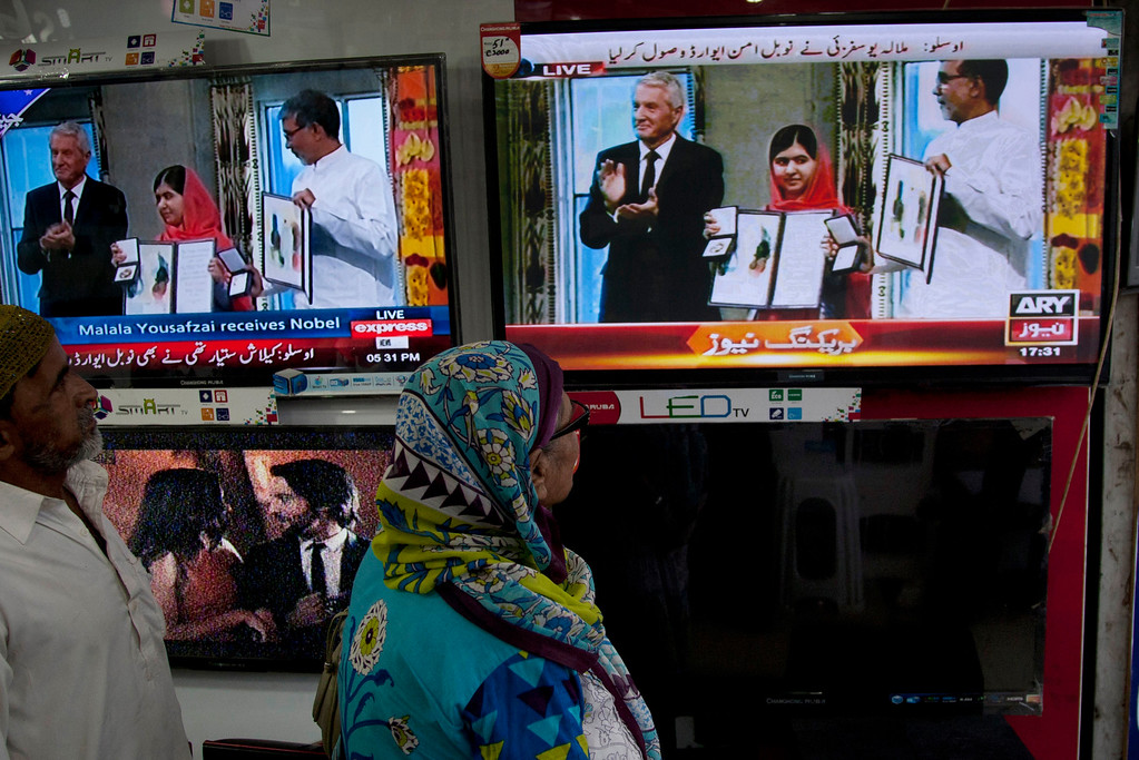 . People watch a live broadcasting of the ceremony of Nobel Peace Prize laureate Malala Yousafzai at a shop in Karachi, Pakistan, Wednesday, Dec. 10, 2014. Malala\'s struggle for girls to be educated in a deeply conservative society led to a shooting against her by the Taliban two years ago. Malala and Kailash Satyarthi of India have received the Nobel Peace Prize for risking their lives to fight for children\'s rights. (AP Photo/Shakil Adil)