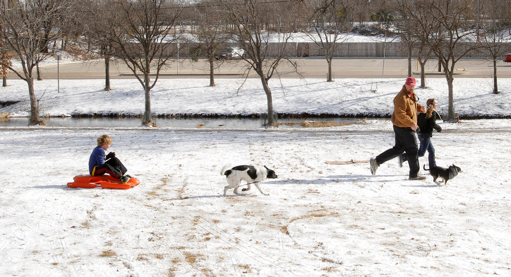 . From left, Gavin Parkhurst, 6, his father Doug Parkhurst and sister Dorian, 10, play in Foster Park in Fort Worth, Texas with their dogs Hank and Max, Wednesday, Dec. 26, 2012, after winter weather covered the area with layer of snow on Christmas Day. (AP Photo/The Fort Worth Star-Telegram, Rodger Mallison)