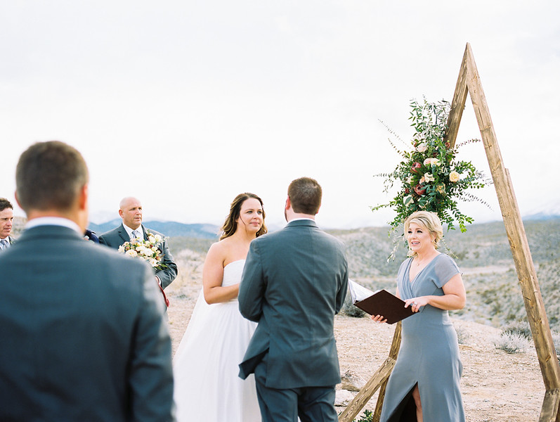 triangle arch with florals for outdoor intimate wedding ceremony // officiant - Peachy Keen Unions //  mountainous, winter, adventure desert elopement - Las Vegas Elopement  & Intimate Wedding Photographer - Kristen Krehbiel - Kristen Kay Photography // Portra 400