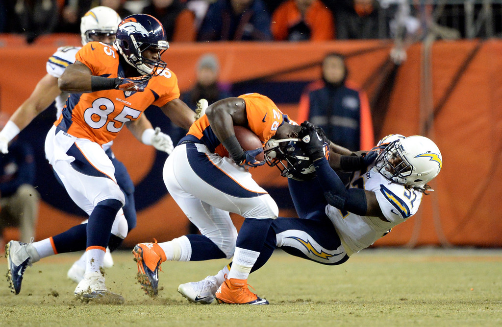 . DENVER, CO - DECEMBER 12: Denver Broncos running back Montee Ball (28) gets his helmet ripped off by San Diego Chargers inside linebacker Reggie Walker (52) during the first half.  The Denver Broncos vs. the San Diego Chargers at Sports Authority Field at Mile High in Denver on December 12, 2013. (Photo by Hyoung Chang/The Denver Post)