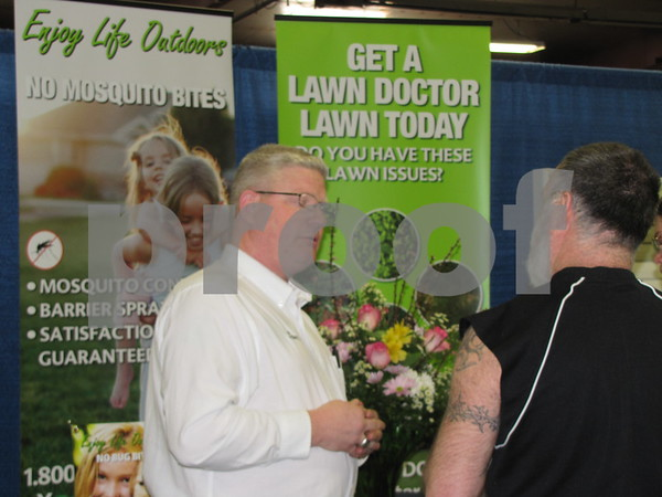 Tom Bowman with 'Lawn Doctor' answers questions for an attendee.