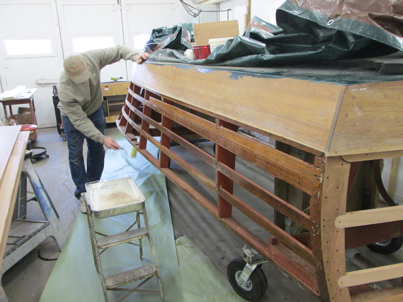 Appling epoxy to the hull so the plywood can be installed.