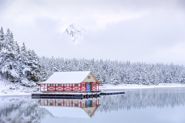 Photograph: Boathouse - A break in the clouds shows Leah Peak above the famous boathouse in Maligne Lake, Alberta, Canada.