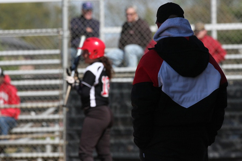 Coach Cole looks on as number 12, Lindsea Hutchinson, prepares to take the plate.