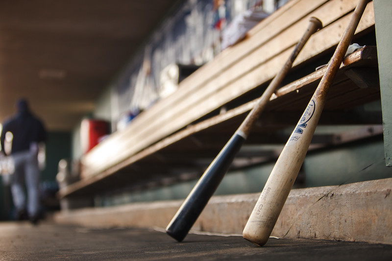Two baseball bats resting on a bench.