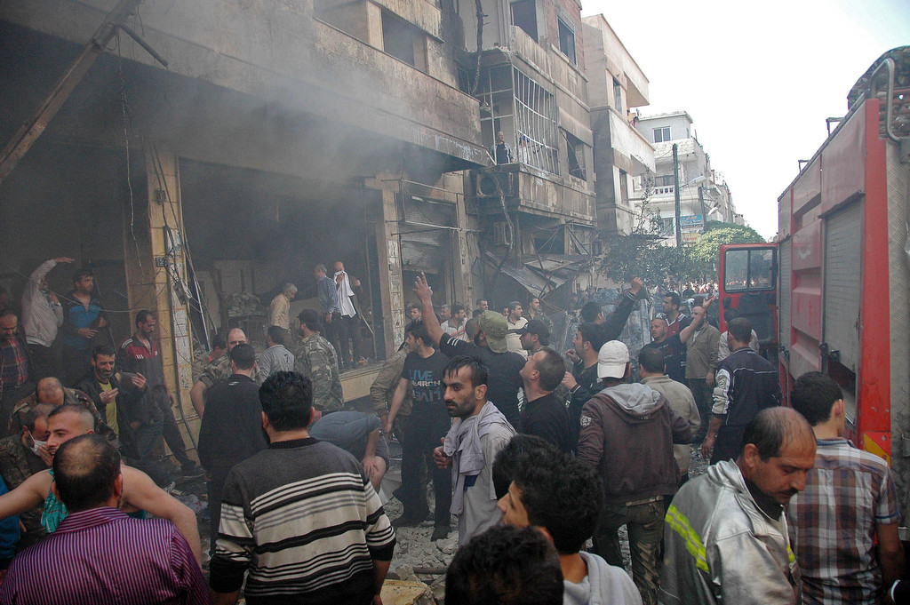 . A handout picture released by the official Syrian Arab News Agency (SANA) shows Syrians gathering at the scene of a car bomb explosion in al-Khudary Street in the Karm al-Loz neighbourhood of the central Syrian city of Homs on April 9, 2014. More than 150,000 people have been killed since the revolt began in March 2011 and nine million have been driven from their homes, including 2.6 million international refugees. (AFP PHOTO /HO/SANA)