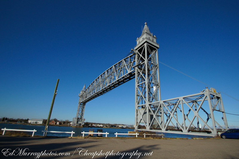 The Cape Cod Canal Railroad Bridge: This is a vertical lift rail road bridge which spans the Cape Code Canal. The bridge was built in 1935 and it has a 544 foot long center span. The bridge is always left in the up position. (Note the huge One thousand ton counter weight within the frame work of the bridge - near it's base.