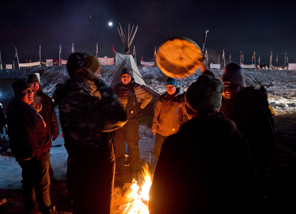 . Campers gather around a fire to sing and drum traditional Native American social songs at the Oceti Sakowin camp where people have gathered to protest the Dakota Access oil pipeline in Cannon Ball, N.D., Sunday, Dec. 4, 2016. U.S. Army Corps of Engineers spokeswoman Moria Kelley said in a news release Sunday that the administration will not allow the four-state, $3.8 billion pipeline to be built under Lake Oahe, a Missouri River reservoir where construction had been on hold. (AP Photo/David Goldman)