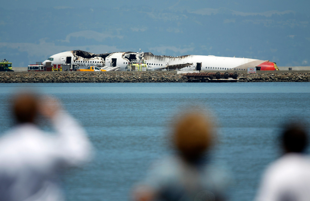 . Onlookers look at the crashed fuselage of Asiana Airlines Flight 214, a Boeing 777 arriving from Seoul, South Korea, on runway 28L at San Francisco International Airport, San Francisco, Calif. on Saturday July 6, 2013.  (LiPo Ching /Bay Area News Group)