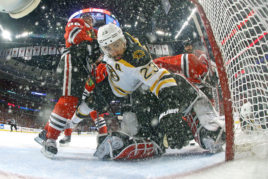. CHICAGO, IL - JUNE 22:  Chris Kelly #23 of the Boston Bruins trips over Corey Crawford #50 of the Chicago Blackhawks in the net during Game Five of the 2013 NHL Stanley Cup Final at United Center on June 22, 2013 in Chicago, Illinois.  (Photo by Bruce Bennett/Getty Images)