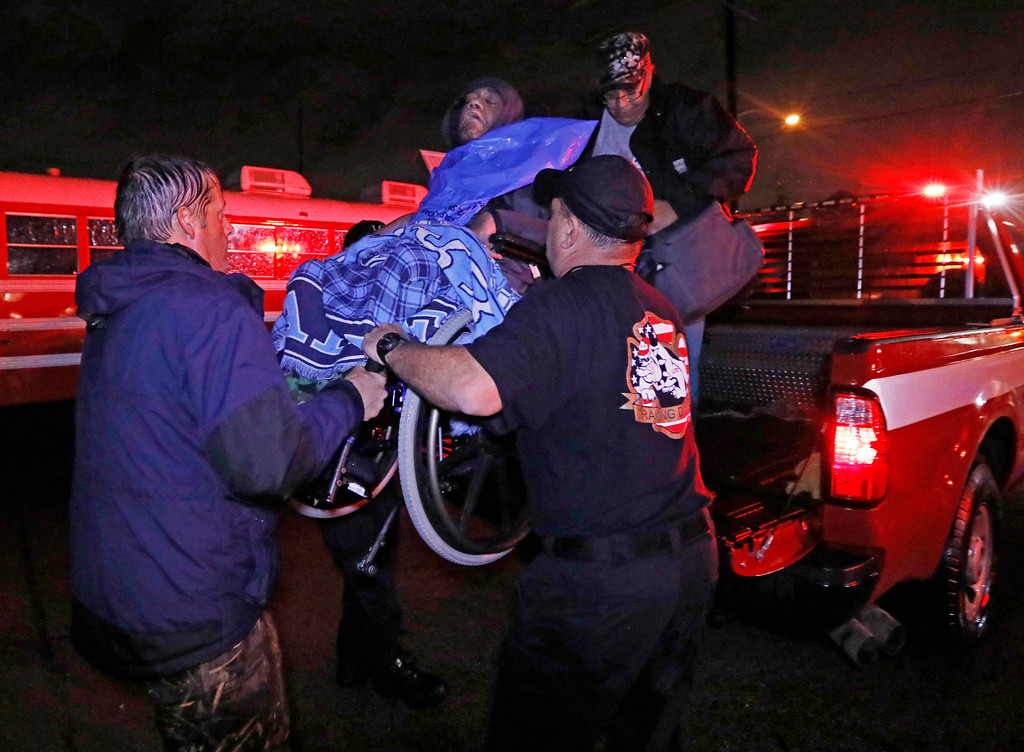 . Lake Charles rescue personnel help lower this wheelchair bound resident from the back of a vehicle late Monday night, Aug. 28, 2017, in Lake Charles, La., after flooding from Harvey\'s almost constant rain over the last two days overcame the city\'s drainage system, flooding several subdivisions and necessitating home rescues. (AP Photo/Rogelio V. Solis)