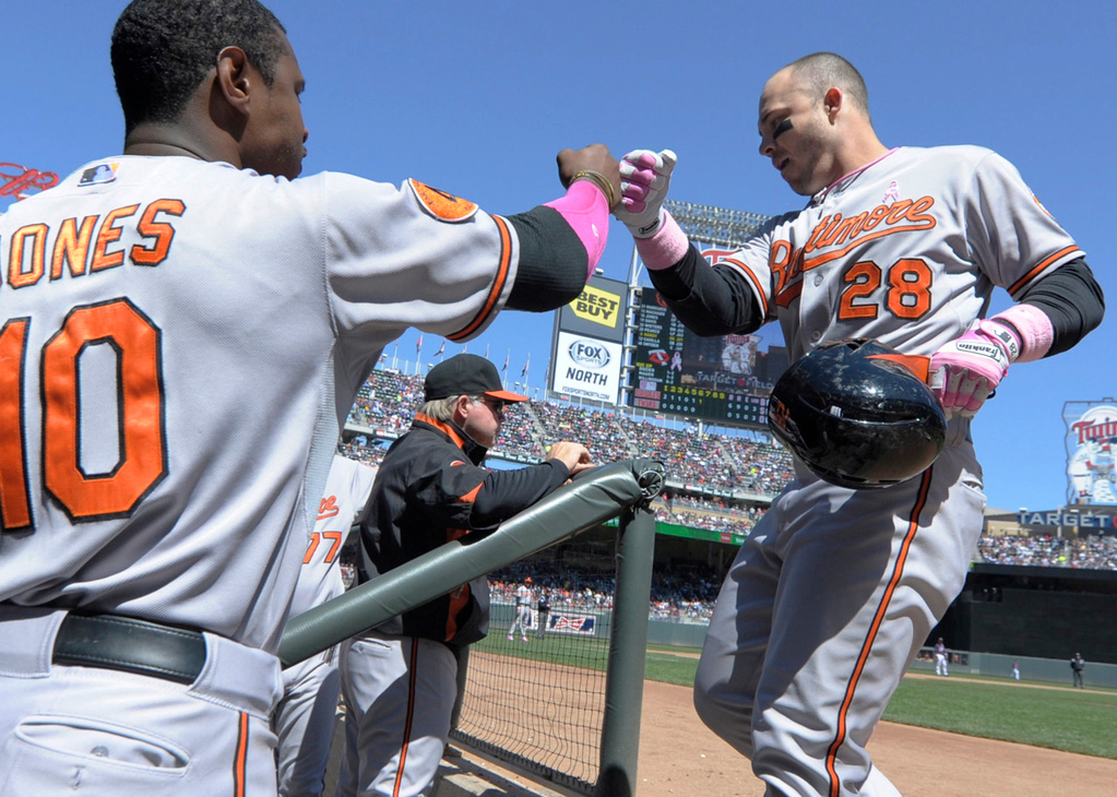 . Baltimore\'s Steve Pearce gets a bump from teammate Adam Jones, left, after his solo homer in the sixth inning against the Twins. (AP Photo/Jim Mone)