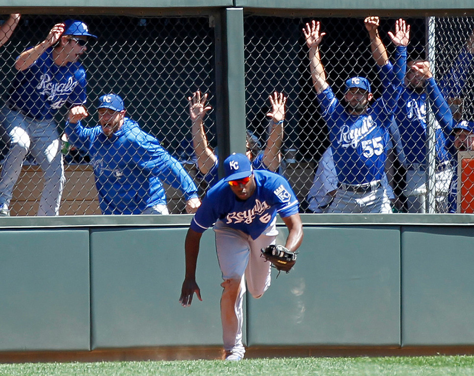 . Royals center fielder Lorenzo Cain comes away from the wall with the ball as the Royals\' bullpen cheers after he robbed Minnesota\'s\' Trevor Plouffe of a home run in the fifth inning. (AP Photo/Andy Clayton-King)