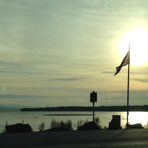 Sunrise behind an American flag next to a lake