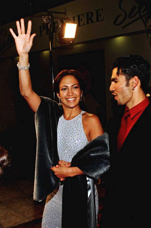 ". HOLLYWOOD, :  Actress Jennifer Lopez (L) waves to fans as she arrives with husband Ojani Noa for the world premiere of the film ""Selena\"" 13 March in Hollywood. Lopez stars in the title role in the movie about the superstar Latina singer, who was tragically murdered by her manager in 1995.  (Vince Bucci/AFP/Getty Images)"
