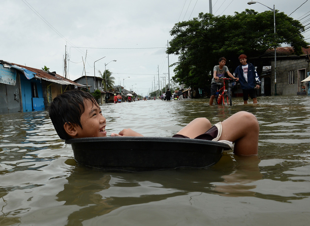 . A boy, one of thousands affected by flooding due to heavy rains exarcebated by Tropical storm Trami, uses a plastic basin to float in the waters along a flooded street in the town of Calumpit, Bulacan province, north of Manila on August 22, 2013. Disaster-weary Philippine residents mopped up August 22 after four days of rains that officials said had killed 18 people and forced more than half a million from flooded homes. TED ALJIBE/AFP/Getty Images