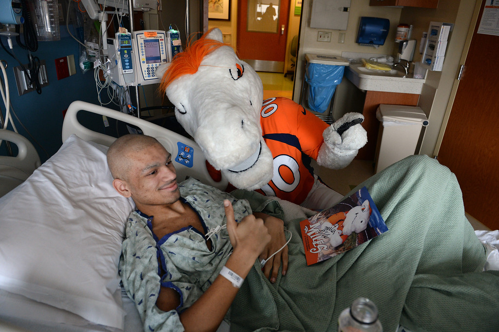 . Lorenzo Caw, 18, has a thumbs up for his parents as they take a picture of him with Miles, the Broncos Mascot, as he made a surprise visit to him in the Pediatric Intensive Care Unit at the  Rocky Mountain Hospital for Children in Denver, Co on January 14, 2014. Caw had surgery to remove a tumor from his right leg caused from osteosarcoma.  (Photo By Helen H. Richardson/ The Denver Post)