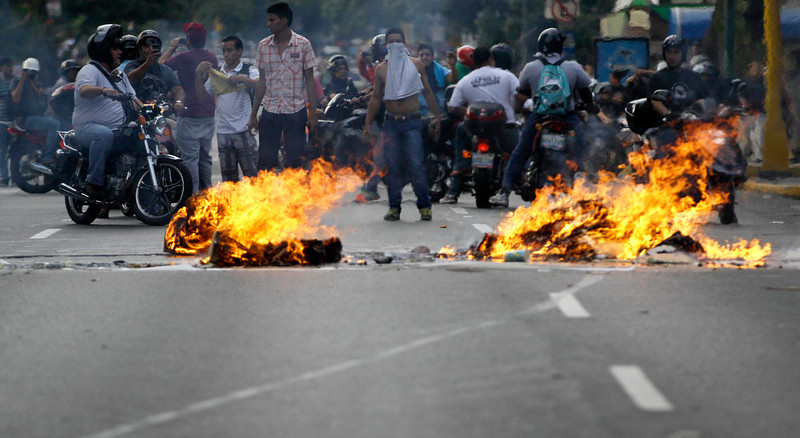 . Opposition supporters burn garbage during clashes with riot police in Caracas, Venezuela, Monday, April 15, 2013. National Guard troops dispersed students protesting the official results of Venezuela\'s disputed presidential election. Opposition candidate Henrique Capriles has challenged his narrow loss to Nicolas Maduro and is demanding a recount. (AP Photo/Fernando Llano )